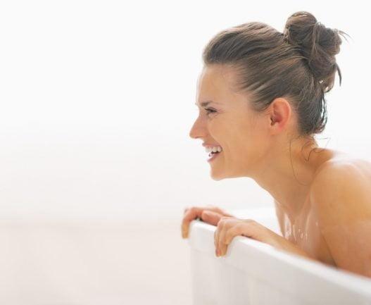 Smilende kvinde i badekar